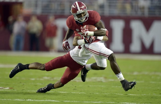 Oct 19, 2013; Tuscaloosa, AL, USA; Alabama Crimson Tide wide receiver Kevin Norwood (83) carries the ball against Arkansas Razorbacks cornerback Jared Collins (29) during the first quarter at Bryant-Denny Stadium. Mandatory Credit: John David Mercer-USA TODAY Sports
