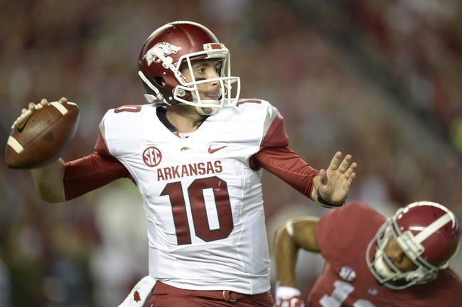 Oct 19, 2013; Tuscaloosa, AL, USA; Arkansas Razorbacks quarterback Brandon Allen (10) rolls out to pass against  the Alabama Crimson Tide defense during the first quarter at Bryant-Denny Stadium. Mandatory Credit: John David Mercer-USA TODAY Sports