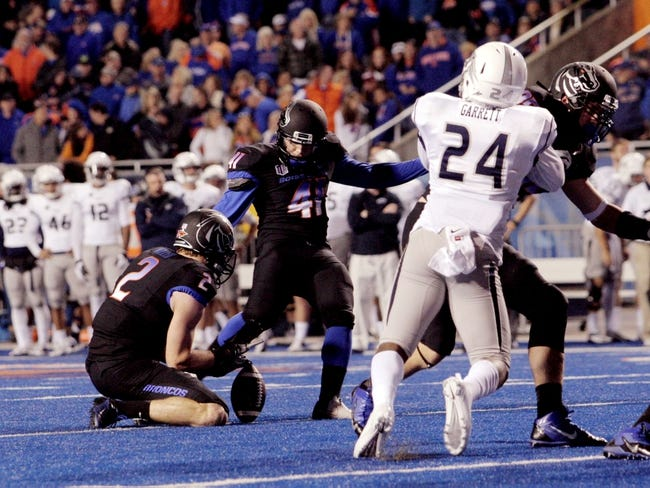 Oct 19, 2013; Boise, ID, USA; Boise State Broncos kicker Dan Goodale (41) kicks and extra point out of the hold of wide receiver Matt Miller (2) during the second half against the Nevada Wolf Pack at Bronco Stadium. The Broncos defeated the Wolf Pack 34-17. Mandatory Credit: Brian Losness-USA TODAY Sports