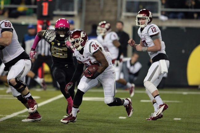 Oct 19, 2013; Eugene, OR, USA; Washington State Cougars quarterback Connor Halliday (12) hands the ball off to Washington State Cougars running back Teondray Caldwell (34) against the Oregon Ducks at Autzen Stadium. Mandatory Credit: Scott Olmos-USA TODAY Sports