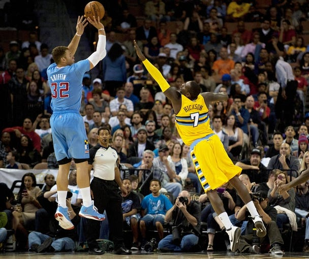 Oct 19, 2013; Las Vegas, NV, USA; Los Angeles Clippers forward Blake Griffin (32) takes a jump shot against a lunging Denver Nuggets forward J.J. Hickson (7) during an NBA preseason game at Mandalay Bay Events Center. Mandatory Credit: Stephen R. Sylvanie-USA TODAY Sports