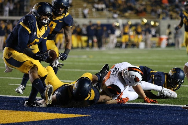 Oct 19, 2013; Berkeley, CA, USA; California Golden Bears safety Michael Lowe (5) recovers the fumble by Oregon State Beavers tight end Caleb Smith (10) during the second quarter at Memorial Stadium. Mandatory Credit: Kelley L Cox-USA TODAY Sports