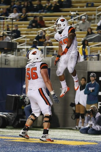 Oct 19, 2013; Berkeley, CA, USA; Oregon State Beavers running back Terron Ward (28) celebrates with center Isaac Seumalo (56) after scoring a touchdown against the California Golden Bears during the fourth quarter at Memorial Stadium. The Oregon State Beavers defeated the California Golden Bears 49-17. Mandatory Credit: Kelley L Cox-USA TODAY Sports