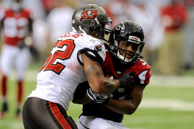 Oct 20, 2013; Atlanta, GA, USA; Atlanta Falcons running back Jacquizz Rodgers (32) is tackled by Tampa Bay Buccaneers outside linebacker Jonathan Casillas (52) during the second half at the Georgia Dome. The Falcons defeated the Buccaneers 31-23.  Mandatory Credit: Dale Zanine-USA TODAY Sports