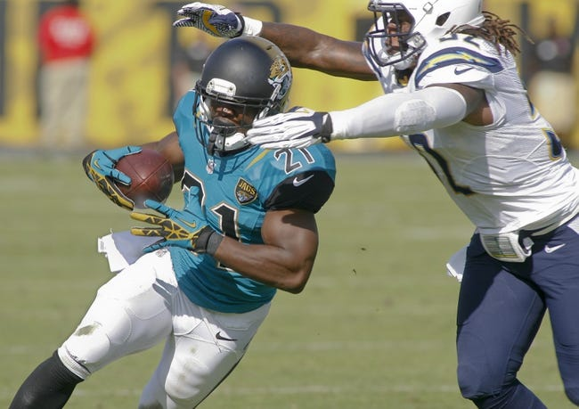 Oct 20, 2013; Jacksonville, FL, USA; Jacksonville Jaguars running back Justin Forsett (21) is tackled by San Diego Chargers outside linebacker Reggie Walker (52) in the fourth quarter of their game at EverBank Field. The San Diego Chargers defeated the Jacksonville Jaguars 24-6. Mandatory Credit: Phil Sears-USA TODAY Sports