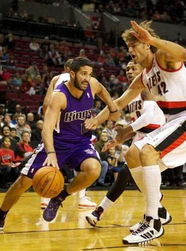 Oct 20, 2013; Portland, OR, USA; Sacramento Kings point guard Greivis Vasquez (10) dribbles around Portland Trail Blazers center Robin Lopez (42) in the first half at Moda Center. Mandatory Credit: Jaime Valdez-USA TODAY Sports