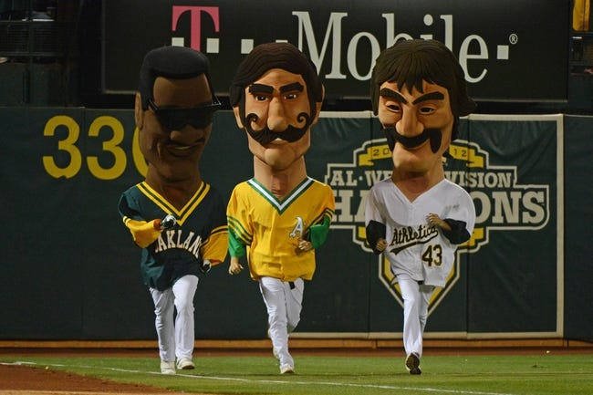 October 4, 2013; Oakland, CA, USA; Oakland Athletics mascots of former players Rickey Henderson (left) and Rollie Fingers (center) and Dennis Eckersley (right) run on the field in a race during the sixth inning in game one of the American League divisional series playoff baseball game against the Detroit Tigers at O.co Coliseum. The Tigers defeated Athletics 3-2. Mandatory Credit: Kyle Terada-USA TODAY Sports
