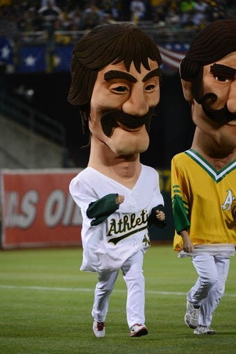 October 5, 2013; Oakland, CA, USA; Oakland Athletics mascot Dennis Eckersley runs the field in a mascot race during the sixth inning in game two of the American League divisional series playoff baseball game against the Detroit Tigers at O.co Coliseum. The Oakland Athletics defeated the Detroit Tigers 1-0. Mandatory Credit: Kyle Terada-USA TODAY Sports
