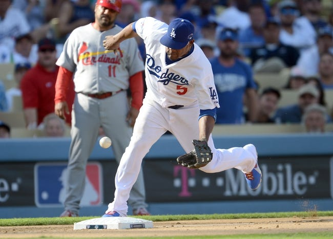 October 16, 2013; Los Angeles, CA, USA;  Los Angeles Dodgers third baseman Juan Uribe (5) fields the ball for an out at third during game five of the National League Championship Series against the St. Louis Cardinals at Dodger Stadium. Mandatory Credit: Jayne Kamin-Oncea-USA TODAY Sports