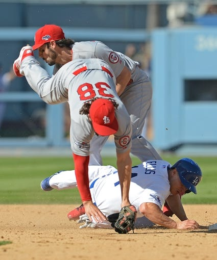 October 16, 2013; Los Angeles, CA, USA; St. Louis Cardinals second baseman Matt Carpenter (13) gets out of the way as shortstop Pete Kozma (38) threw to first to complete a double play in the third inning as Los Angeles Dodgers second baseman Mark Ellis (14) slides into second in game five of the National League Championship Series baseball game at Dodger Stadium. Mandatory Credit: Jayne Kamin-Oncea-USA TODAY Sports