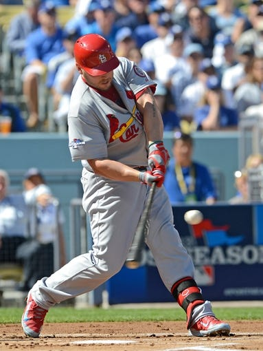 October 16, 2013; Los Angeles, CA, USA; St. Louis Cardinals left fielder Matt Holliday (7) hits a single in the first inning of game five of the National League Championship Series against the Los Angeles Dodgers at Dodger Stadium. Mandatory Credit: Jayne Kamin-Oncea-USA TODAY Sports