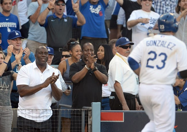 October 16, 2013; Los Angeles, CA, USA; Los Angeles Dodgers owner Magic Johnson reacts after first baseman Adrian Gonzalez (23) hits a solo home run in the ninth inning against the St. Louis Cardinals in game five of the National League Championship Series baseball game at Dodger Stadium. Mandatory Credit: Jayne Kamin-Oncea-USA TODAY Sports