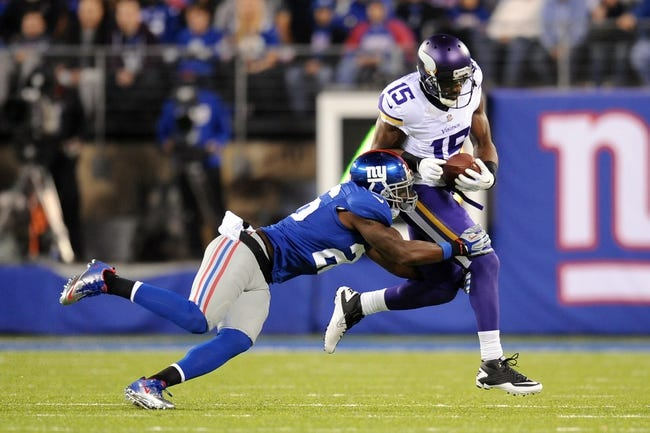 Oct 21, 2013; East Rutherford, NJ, USA; Minnesota Vikings wide receiver Greg Jennings (15) is tackled by New York Giants strong safety Antrel Rolle (26) after making a catch during the first half at MetLife Stadium. The Giants won the game 23-7. Mandatory Credit: Joe Camporeale-USA TODAY Sports