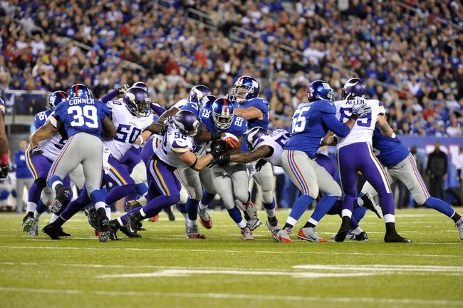 Oct 21, 2013; East Rutherford, NJ, USA; New York Giants running back Michael Cox (29) attempts to run through Minnesota Vikings defenders during the first half at MetLife Stadium. The Giants won the game 23-7. Mandatory Credit: Joe Camporeale-USA TODAY Sports