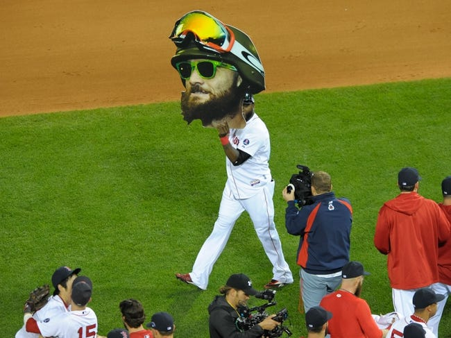 Oct 19, 2013; Boston, MA, USA; Boston Red Sox designated hitter David Ortiz (34) holds a giant Jonny Gomes head after defeating the Detroit Tigers to win the pennant in game six of the American League Championship Series baseball game at Fenway Park. Mandatory Credit: Bob DeChiara-USA TODAY Sports