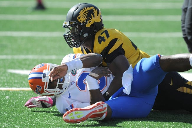 Oct 19, 2013; Columbia, MO, USA; Florida Gators quarterback Tyler Murphy (3) is hit by Missouri Tigers defensive lineman Kony Ealy (47) while throwing during the second half at Faurot Field. Missouri won 36-17. Mandatory Credit: Denny Medley-USA TODAY Sports