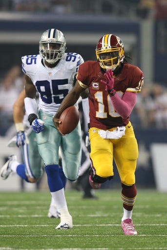 Oct 13, 2013; Arlington, TX, USA; Washington Redskins quarterback Robert Griffin III (10) runs with the ball against Dallas Cowboys defensive end Caeser Rayford (95) at AT&T Stadium. Mandatory Credit: Matthew Emmons-USA TODAY Sports