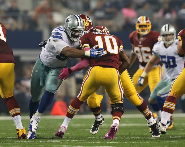 Oct 13, 2013; Arlington, TX, USA; Dallas Cowboys defensive tackle Jason Hatcher (97) sacks Washington Redskins quarterback Robert Griffin III in the second quarter at AT&T Stadium. Mandatory Credit: Matthew Emmons-USA TODAY Sports