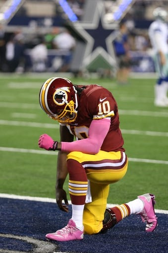Oct 13, 2013; Arlington, TX, USA; Washington Redskins quarterback Robert Griffin III (10) kneels in the end zone for a moment prior to the game against the Dallas Cowboys at AT&T Stadium. Mandatory Credit: Matthew Emmons-USA TODAY Sports