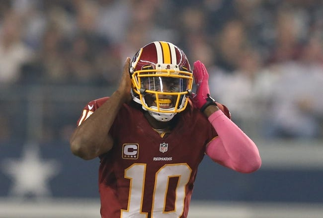 Oct 13, 2013; Arlington, TX, USA; Washington Redskins quarterback Robert Griffin III (10) holds his head to hear as he signals at the line of scrimmage against the Dallas Cowboys at AT&T Stadium. Mandatory Credit: Matthew Emmons-USA TODAY Sports