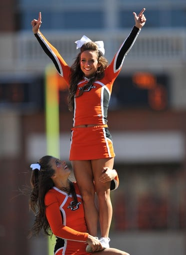 Oct 19, 2013; Stillwater, OK, USA; Members of the Oklahoma State Cowboys cheer squad perform during a game against the Texas Christian Horned Frogs at Boone Pickens Stadium. Mandatory Credit: Peter G. Aiken-USA TODAY Sports