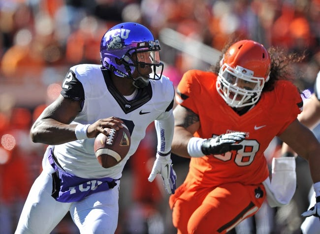 Oct 19, 2013; Stillwater, OK, USA; Texas Christian Horned Frogs quarterback Trevone Boykin (2) scrambles against pressure from Oklahoma State Cowboys defensive tackle Davidell Collins (98) during the first half at Boone Pickens Stadium. Mandatory Credit: Peter G. Aiken-USA TODAY Sports