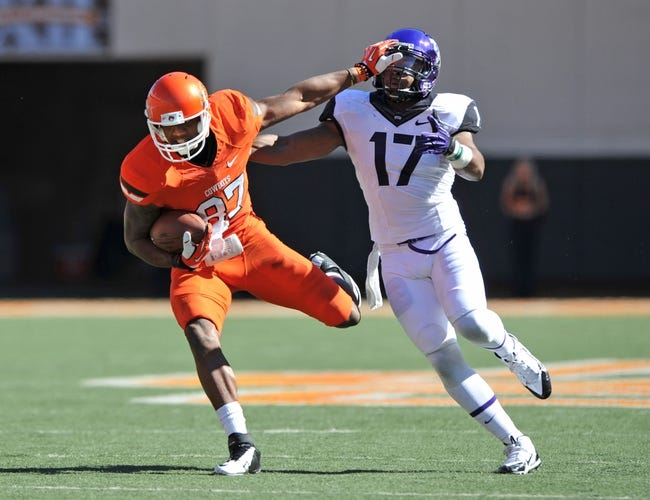 Oct 19, 2013; Stillwater, OK, USA; Oklahoma State Cowboys wide receiver Tracy Moore (87) fights off Texas Christian Horned Frogs safety Sam Carter (17) after catching a pass during the first half at Boone Pickens Stadium. Mandatory Credit: Peter G. Aiken-USA TODAY Sports