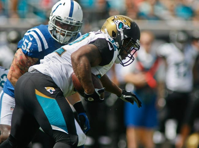 Sep 29, 2013; Jacksonville, FL, USA; Jacksonville Jaguars running back Maurice Jones-Drew (32) runs by Indianapolis Colts linebacker Pat Angerer (51) in the second quarter of their game at EverBank Field. The Indianapolis Colts beat the Jacksonville Jaguars 37-3. Mandatory Credit: Phil Sears-USA TODAY Sports