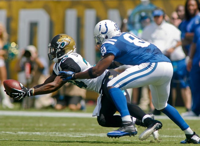 Sep 29, 2013; Jacksonville, FL, USA; Jacksonville Jaguars cornerback Will Blackmon (24) goes for an interception in front of Indianapolis Colts wide receiver Darrius Heyward-Bey (81) in the first quarter of their game at EverBank Field. The Indianapolis Colts beat the Jacksonville Jaguars 37-3. Mandatory Credit: Phil Sears-USA TODAY Sports