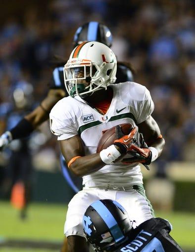 Oct 17, 2013; Chapel Hill, NC, USA; Miami Hurricanes wide receiver Allen Hurns (1) catches the ball as North Carolina Tar Heels cornerback Tim Scott (7) defends in the second quarter at Kenan Memorial Stadium. Mandatory Credit: Bob Donnan-USA TODAY Sports