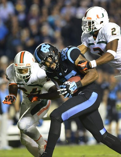 Oct 17, 2013; Chapel Hill, NC, USA; North Carolina Tar Heels tight end Eric Ebron (85) catches the ball as Miami Hurricanes defensive back Rayshawn Jenkins (26) and defensive back Deon Bush (2) defend in the second quarter at Kenan Memorial Stadium. Mandatory Credit: Bob Donnan-USA TODAY Sports
