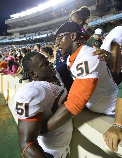 Oct 17, 2013; Chapel Hill, NC, USA; Miami Hurricanes defensive lineman Shayon Green (51) with fans after the game. The Miami Hurricanes defeated the North Carolina Tar Heels 27-23 at Kenan Memorial Stadium. Mandatory Credit: Bob Donnan-USA TODAY Sports