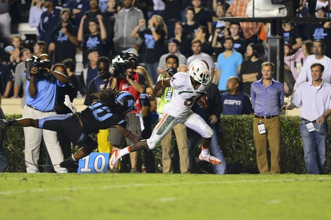 Oct 17, 2013; Chapel Hill, NC, USA; Miami Hurricanes wide receiver Herb Waters (6) is pushed out of bounds by North Carolina Tar Heels safety Tre Boston (10) in the fourth quarter. The Miami Hurricanes defeated the North Carolina Tar Heels 27-23 at Kenan Memorial Stadium. Mandatory Credit: Bob Donnan-USA TODAY Sports