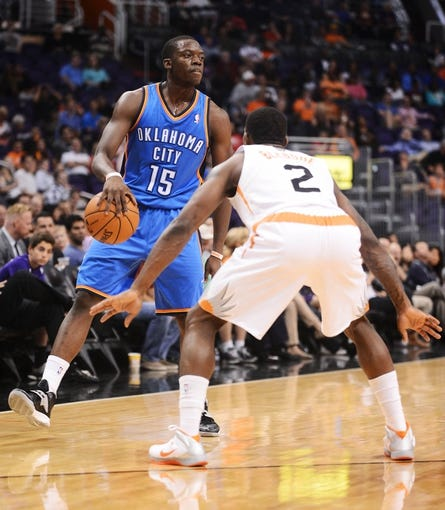Oct 22, 2013; Phoenix, AZ, USA; Oklahoma City Thunder guard Reggie Jackson (15) handles the ball against defender Phoenix Suns guard Eric Bledsoe (2) in the first half at US Airways Center. Mandatory Credit: Jennifer Stewart-USA TODAY Sports
