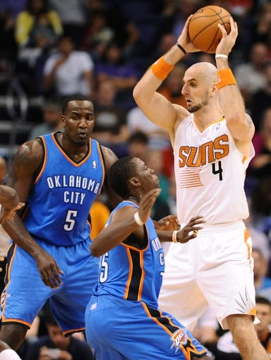 Oct 22, 2013; Phoenix, AZ, USA;Phoenix Suns center Marcin Gortat (4) handles the ball against defender Oklahoma City Thunder guard Reggie Jackson (15) in the first half at US Airways Center. Mandatory Credit: Jennifer Stewart-USA TODAY Sports