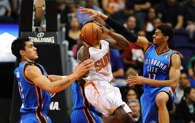 Oct 22, 2013; Phoenix, AZ, USA;Phoenix Suns guard Eric Bledsoe (2) makes a pass in traffic against the Oklahoma City Thunder center Steven Adams (12) and guard Jeremy Lamb (11) in the first half at US Airways Center. Mandatory Credit: Jennifer Stewart-USA TODAY Sports