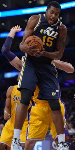 Oct 22, 2013; Los Angeles, CA, USA;  Utah Jazz power forward Derrick Favors (15) grabs a rebound in front of Los Angeles Lakers power forward Pau Gasol (16) during second quarter action at Staples Center. Mandatory Credit: Robert Hanashiro-USA TODAY Sports