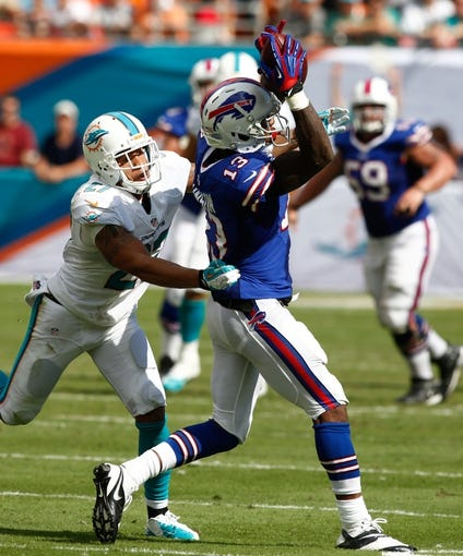 Oct 20, 2013; Miami Gardens, FL, USA; Buffalo Bills wide receiver Steve Johnson (13) catches a pass against Miami Dolphins safety Jimmy Wilson (27) in the second half at Sun Life Stadium. The Bills won 23-21. Mandatory Credit: Robert Mayer-USA TODAY Sports