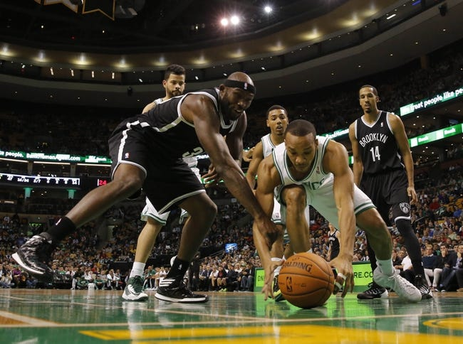 Oct 23, 2013; Boston, MA, USA; Boston Celtics point guard Avery Bradley (0) works for the loose ball against Brooklyn Nets power forward Reggie Evans (30) during the second quarter at TD Garden. Mandatory Credit: David Butler II-USA TODAY Sports