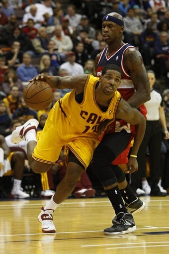 Oct 23, 2013; Cincinnati, OH, USA; Cleveland Cavaliers forward Tristan Thompson (13) moves against Washington Wizards forward Al Harrington (7) during the first half at US Bank Arena. Mandatory Credit: David Kohl-USA TODAY Sports