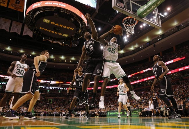 Oct 23, 2013; Boston, MA, USA; Boston Celtics small forward Gerald Wallace (45) grabs the rebound against Brooklyn Nets power forward Reggie Evans (30) during the second half at TD Garden. The Celtics defeated the Brooklyn Nets 101-97. Mandatory Credit: David Butler II-USA TODAY Sports