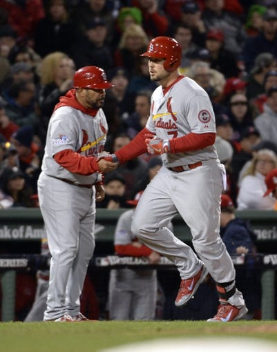 Oct 23, 2013; Boston, MA, USA; St. Louis Cardinals left fielder Matt Holliday (7) is congratulated by third base coach Jose Oquendo (left) after hitting a solo home run against the Boston Red Sox in the 9th inning during game one of the MLB baseball World Series at Fenway Park. Mandatory Credit: Robert Deutsch-USA TODAY Sports