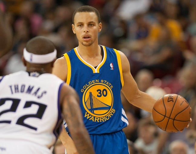 Oct 23, 2013; Sacramento, CA, USA; Golden State Warriors point guard Stephen Curry (30) brings the ball up the court during the second quarter against Sacramento Kings point guard Isaiah Thomas (22) at Sleep Train Arena. Mandatory Credit: Ed Szczepanski-USA TODAY Sports