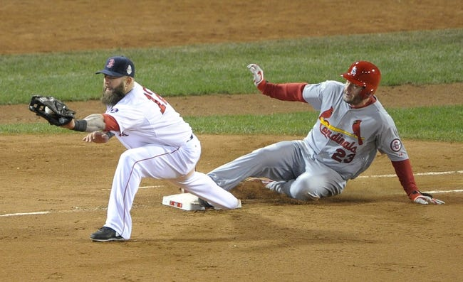 Oct 23, 2013; Boston, MA, USA; St. Louis Cardinals third baseman David Freese (23) slides safely into first base with a single ahead of the throw to Boston Red Sox first baseman Mike Napoli (12) in the 9th inning during game one of the MLB baseball World Series at Fenway Park. Mandatory Credit: Bob DeChiara-USA TODAY Sports