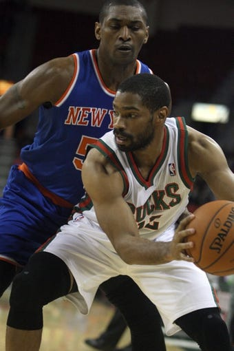 Oct 23, 2013; Green Bay, WI, USA; Milwaukee Bucks guard Gary Neal (right) controls the ball as New York Knicks forward World Peace (51) defends at the Resch Center in Green Bay.  The Milwaukee Bucks defeated the New York Knicks 105-95. Mandatory Credit: Mary Langenfeld-USA TODAY Sports