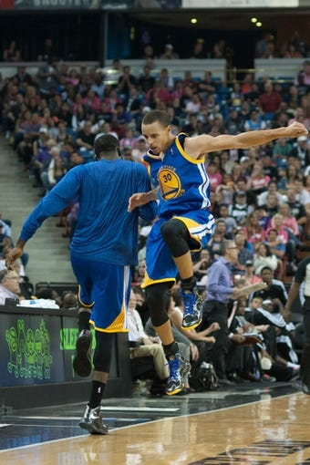 Oct 23, 2013; Sacramento, CA, USA; Golden State Warriors point guard Stephen Curry (30) celebrates with a teammate after scoring against the Sacramento Kings during the fourth quarter at Sleep Train Arena. The Sacramento Kings defeated the Golden State Warriors 91-90. Mandatory Credit: Ed Szczepanski-USA TODAY Sports