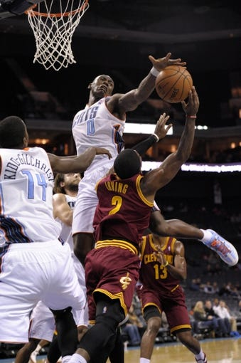 Oct 24, 2013; Charlotte, NC, USA; Charlotte Bobcats forward center Bismack Biyombo (0) blocks the shot of Cleveland Cavaliers guard Kyrie Irving (2) during the game at Time Warner Cable Arena. Mandatory Credit: Sam Sharpe-USA TODAY Sports