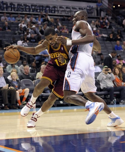 Oct 24, 2013; Charlotte, NC, USA; Cleveland Cavaliers forward center Tristan Thompson (13) drives past Charlotte Bobcats forward center Bismack Biyombo (0) during the game at Time Warner Cable Arena. Mandatory Credit: Sam Sharpe-USA TODAY Sports