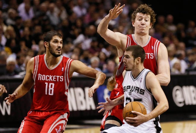 Oct 24, 2013; San Antonio, TX, USA; San Antonio Spurs guard Nando De Colo (25) drives to the basket as Houston Rockets center Omer Asik (behind) defends during the first half at AT&T Center. Mandatory Credit: Soobum Im-USA TODAY Sports