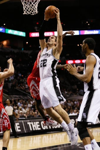 Oct 24, 2013; San Antonio, TX, USA; San Antonio Spurs forward Tiago Splitter (22) dunks past Houston Rockets guard Patrick Beverley (behind) during the first half at AT&T Center. Mandatory Credit: Soobum Im-USA TODAY Sports